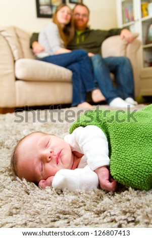 A newborn baby boy sleeps on the floor with his parents behind him slightly out of focus. The three people are in the living room of the mother and father's house.
