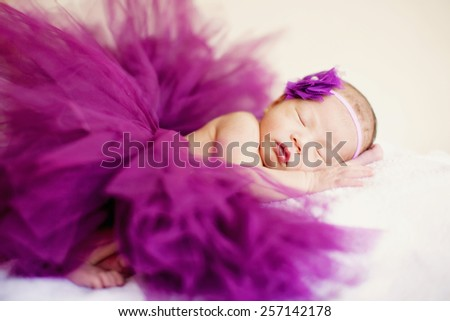 A newborn baby girl is sleeping, dressing purple cloths, which looks like a skirt, with a purple headdress, shot just three days after born