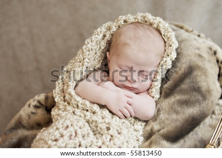 A newborn baby girl snuggled in a warm blanket cocoon, selective focus with focus on face - stock photo