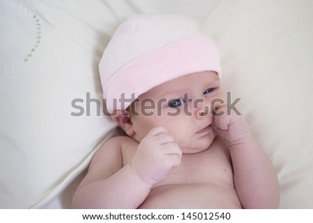 A newborn baby girl with a pink hat, sucking her thumb - stock photo