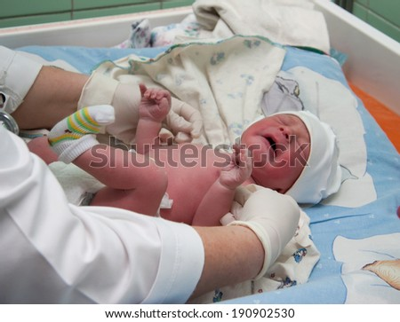 A newborn baby in the hospital - the first minutes of the new life - stock photo