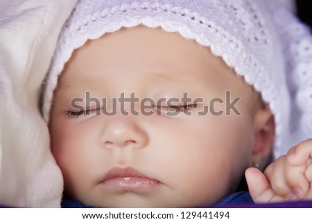 A newborn baby is wearing a white hat and sleeping - stock photo