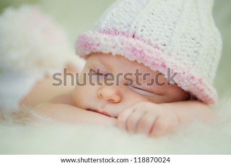 A newborn baby is wearing a white hat and sleeping on a soft white background. Childhood or parenting concept. - stock photo