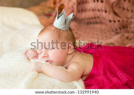A newborn baby is wearing in a princess costume and sleeping on a soft white background. Childhood or parenting concept. - stock photo