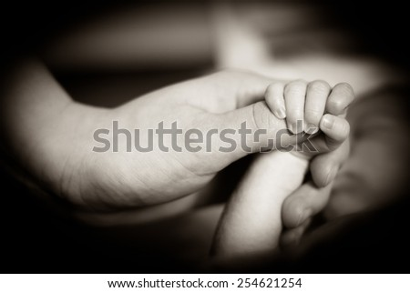 A newborn child is holding the finger of his mother with his little hand.