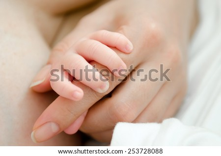A newborn child's hand holding its mother finger - stock photo