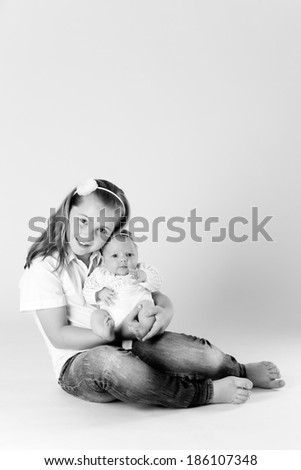 A newborn little girl with her big sister. Family, love, caring.  - stock photo