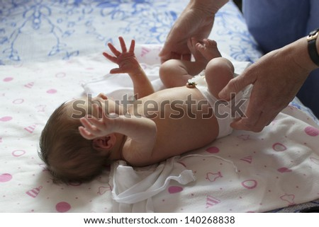 A newborn (1 week old) baby being examined by a pediatrician - stock photo