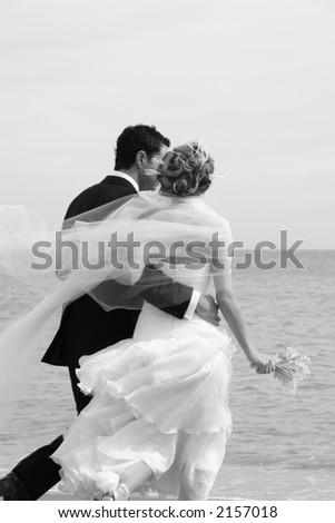 A newly married couple on a romantic walk along the beach - stock photo
