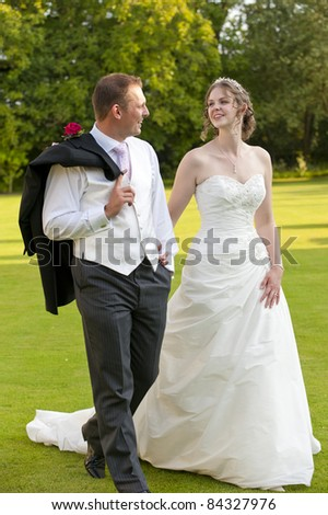 A newly wed Bride and Groom walking hand in hand in the late evening sunshine - stock photo