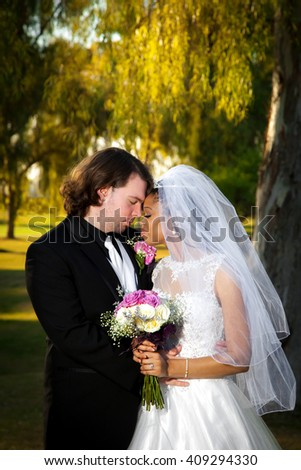 A newly wed couple leans together with foreheads pressed against each other.  Their eyes are closed as they take a moment to reflect on their wedding day.   - stock photo