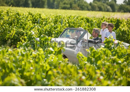 A newlywed couple is driving a convertible retro car on a country road with their two beautiful children. - stock photo