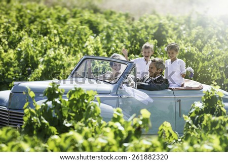 A newlywed couple is driving a convertible retro car on a country road with their two beautiful children - stock photo