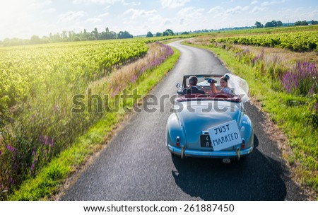 A newlywed couple is driving a convertible retro car, the bride is looking at camera with her bouquet. - stock photo
