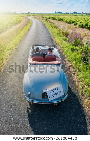 A newlywed couple is driving a retro car on a country road for their honeymoon, top view - stock photo