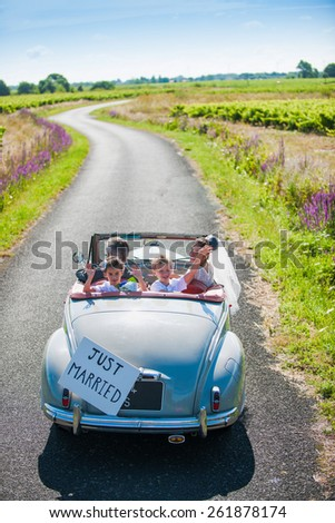 A newlywed couple is driving a retro car on a country road with their two beautiful children. Top view - stock photo
