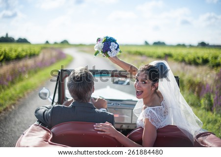 A newlywed couple is driving a retro car, the bride looks at the camera and throws her bouquet, rear view - stock photo