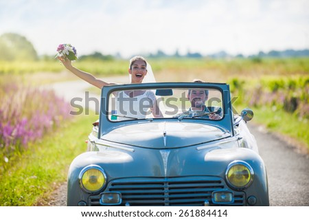 A newlywed couple on a lovely country road for their honeymoon. The bride is lifting her bouquet. - stock photo
