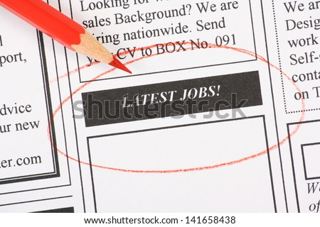 A newspaper column in the classifieds with the Latest Jobs section circled with a red pencil - stock photo