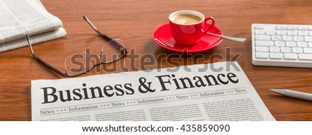 A newspaper on a wooden desk - Business and Finance - stock photo