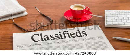 A newspaper on a wooden desk - Classifieds - stock photo