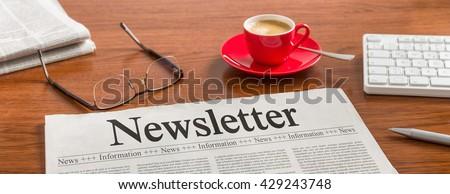 A newspaper on a wooden desk - Newsletter - stock photo