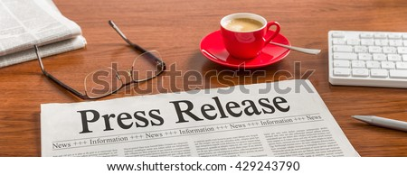 A newspaper on a wooden desk - Press Release - stock photo
