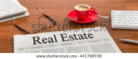 A newspaper on a wooden desk - Real Estate - stock photo