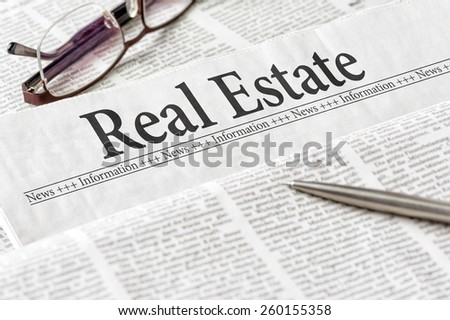 A newspaper with the headline Real Estate - stock photo