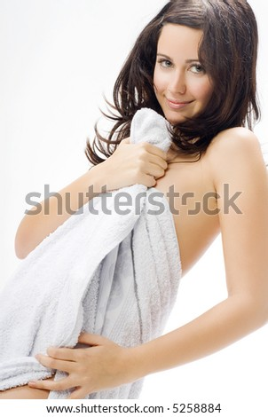 a nice brunette with white towel taking pose in front of the camera playing and smiling - stock photo