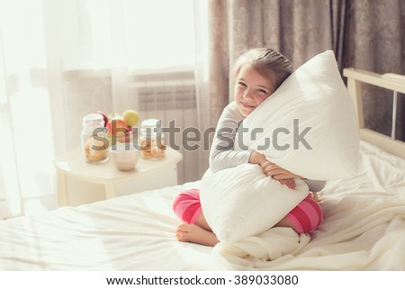 A nice child girl enjoys sunny morning. Good morning at home. Child girl wakes up from sleep. A close up portrait of a sweet smiling little girl waking up and lying in bed in the morning - stock photo