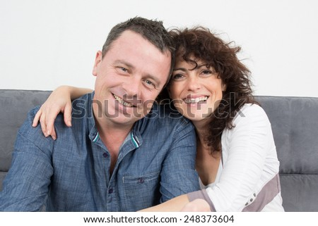 A nice couple smiling at camera at home in their living room