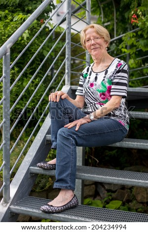 A nice elderly woman smiles sits on stairs in a garden and smile