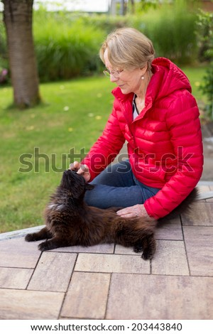 A nice elderly woman strokes her cat passionately - stock photo