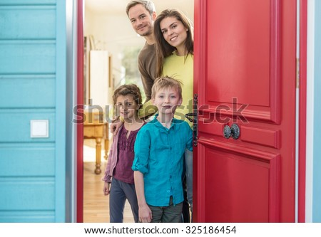 A nice four people family is opening their stylish red door to welcome the guest. The parents and their two children are smiling and wearing casual clothes. The house have blue wall and wooden floors - stock photo