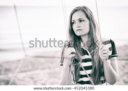 A nice girl holding a ropes. It is a part of boat placed on a beach. Black and white photo. - stock photo