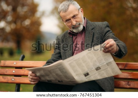 A nice grandfather with a beautiful beard in a gray jacket sits on a bench in the park and reads a newspaper