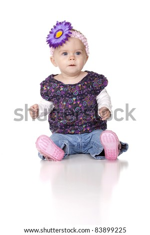 A nice image of an 8 month old baby isolated with reflection on white.  The cute baby girl has a purple bow in her hair.