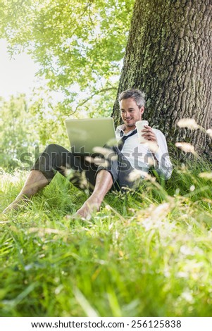 A nice looking grey hair business man is sitting against a tree in the grass, drinking coffee with his computer on his knees. He is relaxing, enjoying the shadow of the tree in a sunny day.