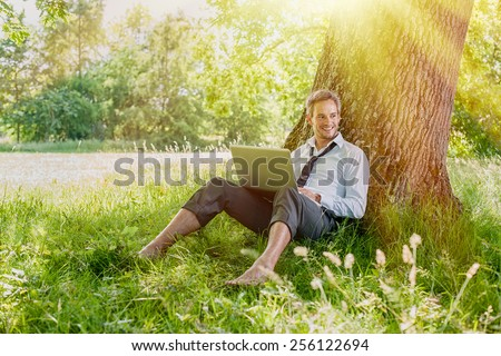 A nice looking grey hair man is sitting against a tree in the grass, looking at his computer. He is relaxing, enjoying the shadow of the tree in a sunny day. - stock photo