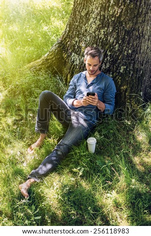 A nice looking grey hair man is sitting against a tree in the grass, looking at his smartphone; his coffee next to him. He is relaxing, enjoying the shadow of the tree in a sunny day.