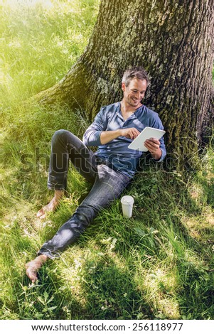A nice looking grey hair man is sitting against a tree in the grass, looking at his tablet ; his coffee next to him. He is relaxing, enjoying the shadow of the tree in a sunny day.