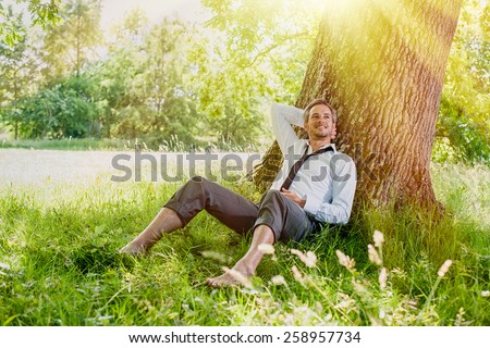 A nice looking man is sitting against a tree in the grass, looking like he is dreaming awake.  He is relaxing, enjoying the shadow of the tree in a sunny day. - stock photo
