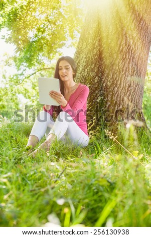 A nice looking woman is sitting against a tree in the grass, looking at her tablet. She is relaxing, enjoying the shadow of the tree in a sunny day. - stock photo