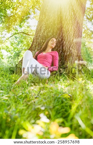 A nice looking woman is sitting against a tree in the grass, looking like she is dreaming. She is relaxing, enjoying the shadow of the tree in a sunny day.