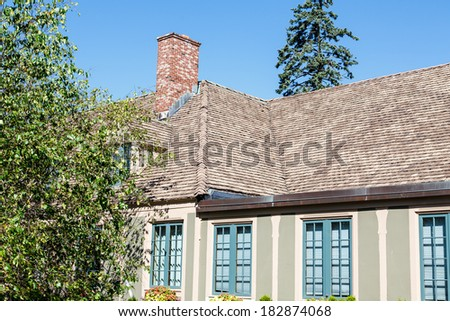 A nice plaster home with shingled roof - stock photo