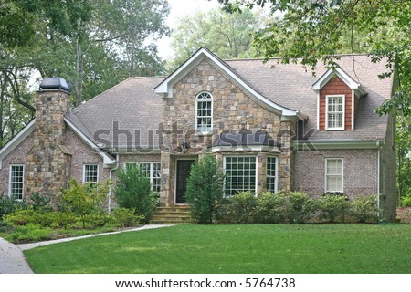A nice stone and brick house on a grassy hill