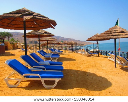 A nice sunny day at the Dead Sea resort. Blue beach chairs and umbrellas waiting for tourists. - stock photo