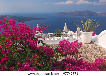A nice terrace in Santorini island with bougainvillea flowers and the view over the caldera. Greece - stock photo