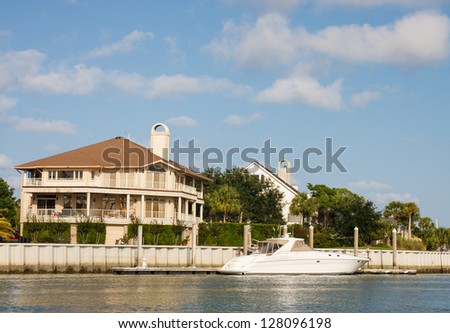 A nice three story home on a channel with a small white yacht anchored at dock - stock photo
